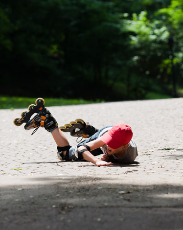 Little boy roller-skating falls by accident. He suffer and shows face of pain photo