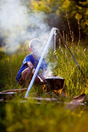 Petit garçon cuisine sur un feu dans le camping sauvage La fumée