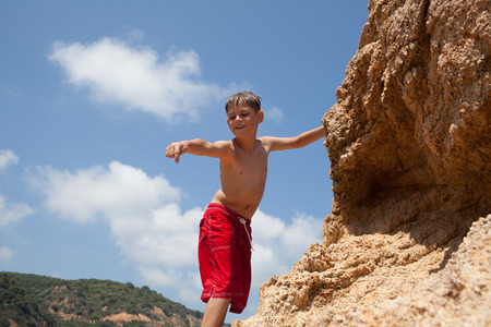Attractive little boy pointing index finger down, climbing on cliff photo