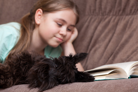 Little girl with dog reading book while lying on the sofa at home. Focus on foreground photo