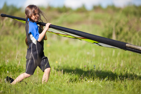 Little girl wearing a sail to the water, ready for windsurfing photo