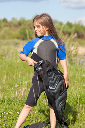 trapeze: Cute little girl in wetsuit with trapeze