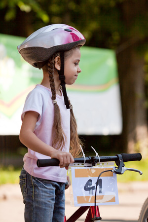 Six year old girl with bicycle wearing a bike helmet photo