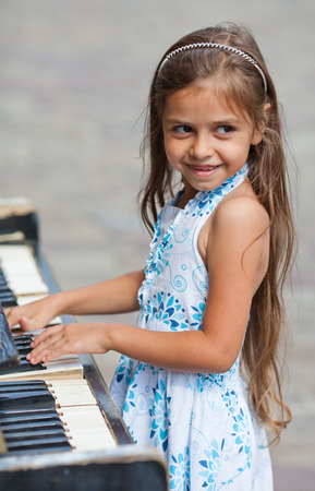 Little girl playing on  old black piano outdoors