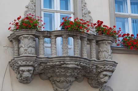 heads old building facade: Two windows and flowered balcony on the Market Square in Lviv, Ukraine
