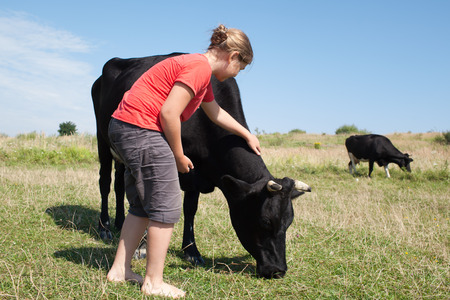 Young girl petting a friendly cow outdoors