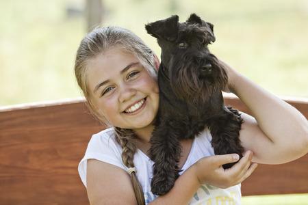 Portrait d'une belle jeune fille tenant son chien tout en profitant un jour d'été