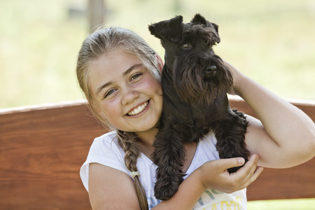 Portrait of a beautiful young girl holding her dog while enjoying a summer day Фото со стока