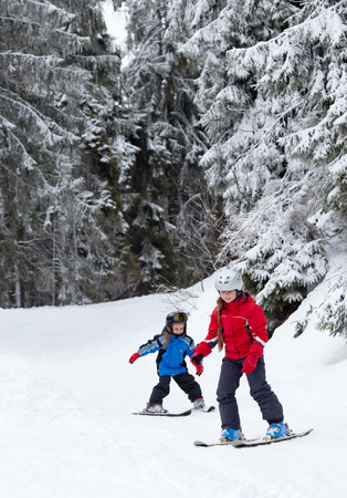 Teanage girl with her little sister skiing in the forest