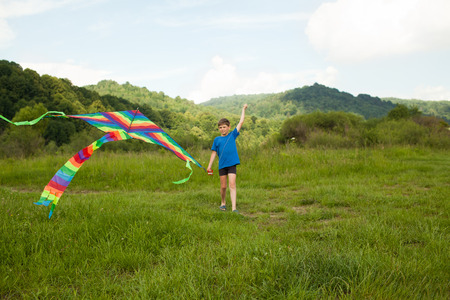 non urban 1: Happy boy playing in field with multicolor kite