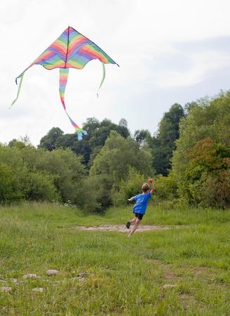 papalote: Muchacho feliz que juega en el campo con la cometa multicolor