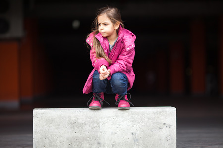 squatting down: A sad little girl crouching down in pink