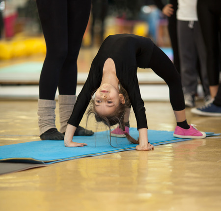 Little girl making exercises on floor mat in bodysuit