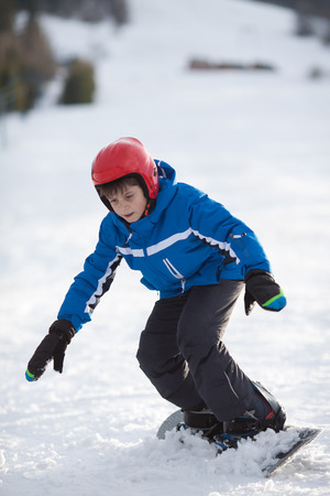 young boy: Cute young boy on snowboard on a snow covered hill Stock Photo