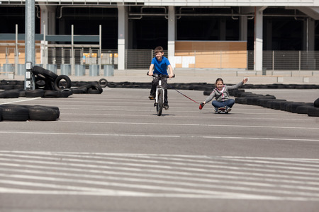 two girls: Young girl on skateboard following little boy on bicycle in a sports track