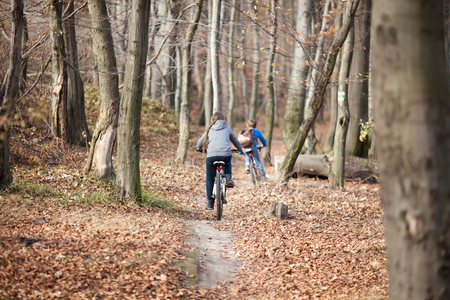 Two children on bicycles in autumn forest