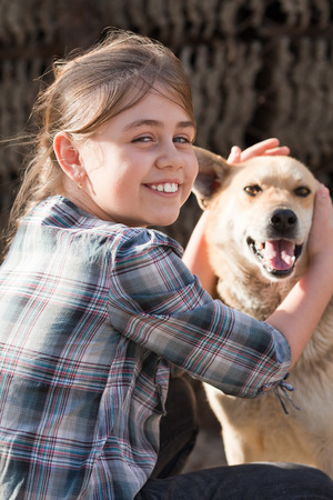 candid: Candid young girl holding stray dog. Positive feeling