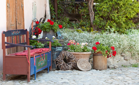 patio: Wooden bench, decorations and flowers in the patio. Relaxation place near home
