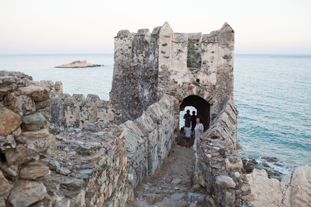 Family looking medieval fortress. Maumere fortress and sea near Anamur, Turkey photo