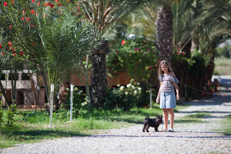 Girl walking with dog in garden photo