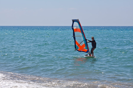 Windsurfing in a calm day with clear blue sky and Mediterranean Sea photo