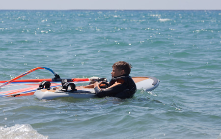 Little windsurfer in a calm day with equipment photo
