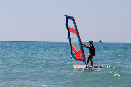 Windsurfing in a calm day with clear blue sky and Mediterranean Sea. Ship in the background photo
