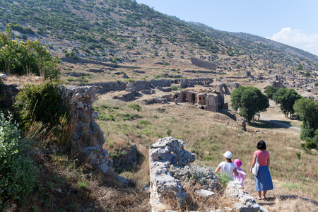 Family in old city Anemurium.  Anemurium is an ancient city whose ruins, now called Eski Anamur or Anemuryum, are close to the modern Turkish city of Anamur. It was in the Roman province of Isauria and was situated near a Cape Anamur, only 64 km from Cypr photo
