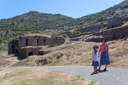 Mother and daughter in old city Anemurium.  Anemurium is an ancient city whose ruins, now called Eski Anamur or Anemuryum, are close to the modern Turkish city of Anamur. It was in the Roman province of Isauria and was situated near a Cape Anamur, only 64 photo