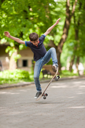 Little skateboarder balancing in mid-air with skateboard photo