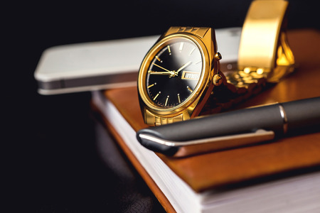 Men accessory, golden watch, pen and mobile phone on the leather diary. Standard-Bild