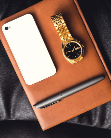 white collar crime: Men accessory, golden watch, pen and mobile phone on the leather diary. Stock Photo
