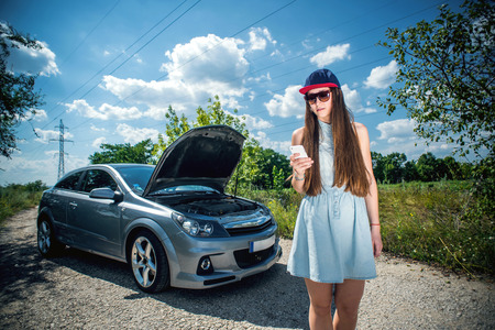 engine bonnet: Young woman near broken car speaking by phone needs assistance.