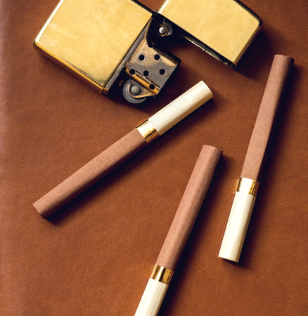 accesory: Mens accesory, golden lighter and cigarettes on a brown leather background..