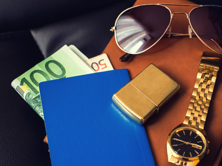 accesory: Travellers accesory, passport, money, golden watch, sunglasses and lighter on the leather diary