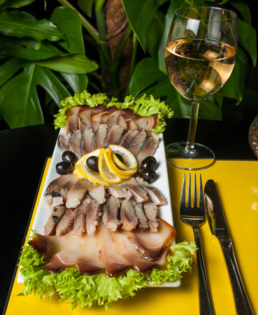 meat alternatives: Herring decorated with lemon, onion and parsley on a yellow and black background with a glass of wine.