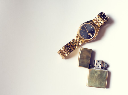 chronograph: Mens accesory, golden watch and lighter on white background.