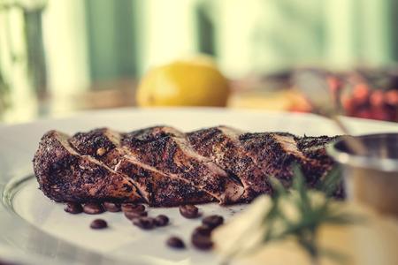 Heerlijk biefstuk met tomatensaus, meloen en rozemarijn, versierd met koffiebonen op de plaat, houten tafel. herfst concept. Selectieve aandacht.