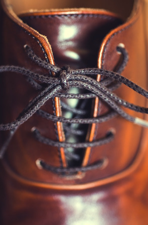 men s feet: A vertical close up of laces on a brown leather business shoe. Stock Photo
