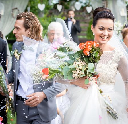 sotto la pioggia: Appena coppia sposata sotto una pioggia di petali di rosa.