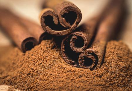 Cinnamon sticks with cinnamon powder on wooden background,