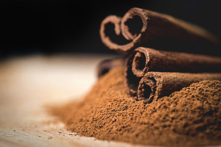 Cinnamon sticks with cinnamon powder on wooden background,