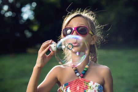 Cute little girl is blowing a soap bubbles photo