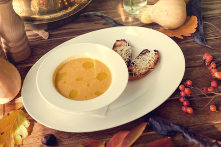 crouton: Bowl of pumpkin soup with bread crouton on white wood table