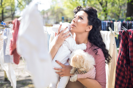 Mother with baby doing laundry outdoors.