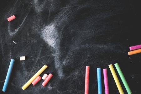 Zwarte oude leeg bord voor kopieer ruimte met kleurrijke stukjes krijt. Stockfoto