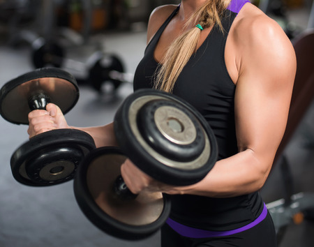 athletic woman pumping up muscles with dumbbells. Banco de Imagens