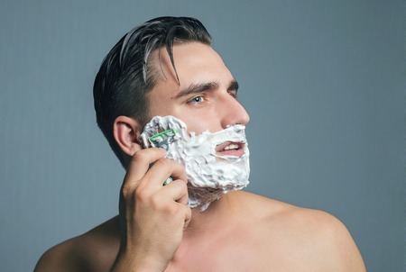 razor blade: Young man shaving with razor and foam.