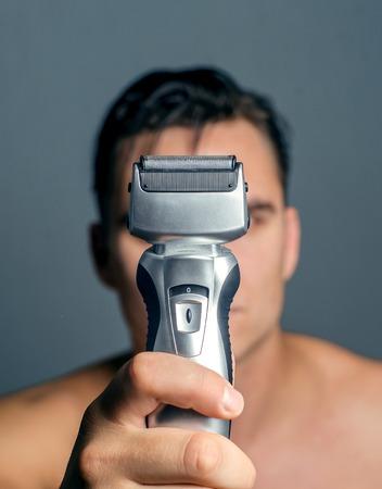 electric shaver: mano che tiene un rasoio elettrico. Archivio Fotografico