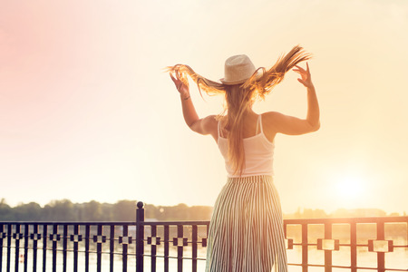 happy girl in a hat walking in a city park. Shooting at sunset Banco de Imagens